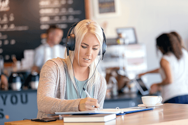 student wearing headphones and writing